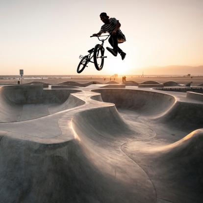 A BMX biker at the bike park at sunset.