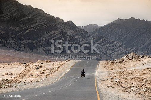 Biker ride through a desert alone with vintage motorbike