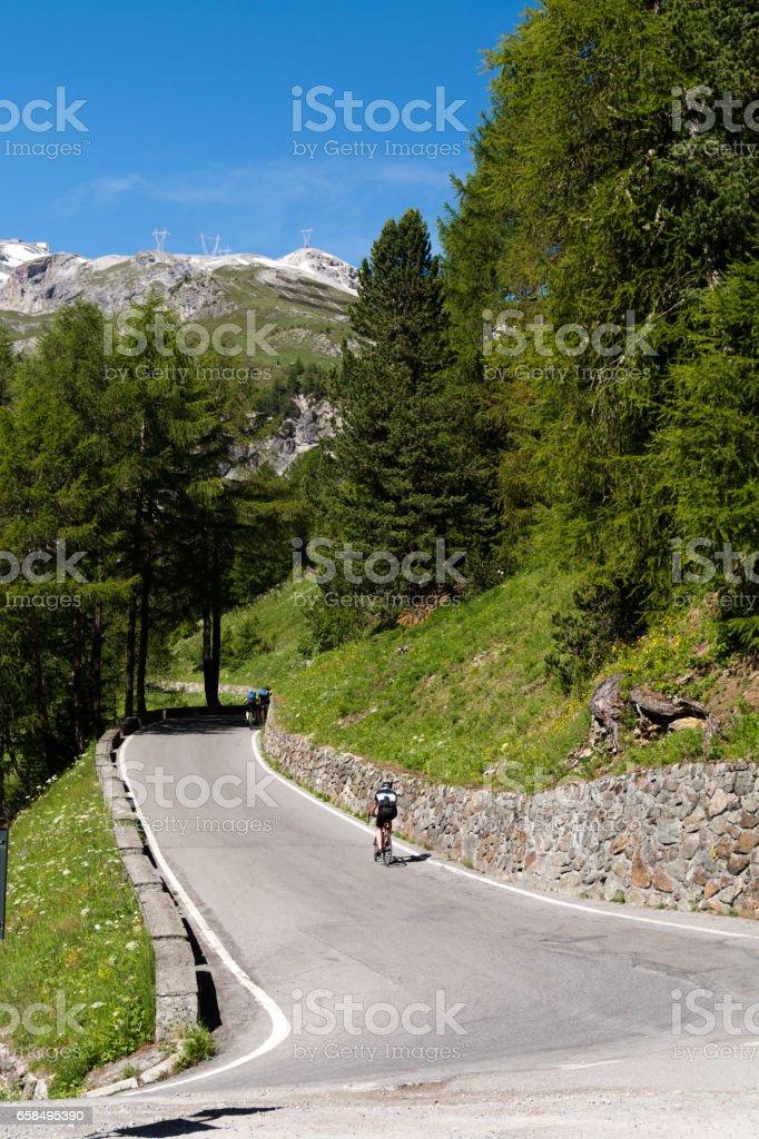 Biker rides serpentine mountain road stock photo