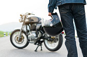 istock Biker riding in jean is holding a helmet and  motorcycle blur background. 1156610253