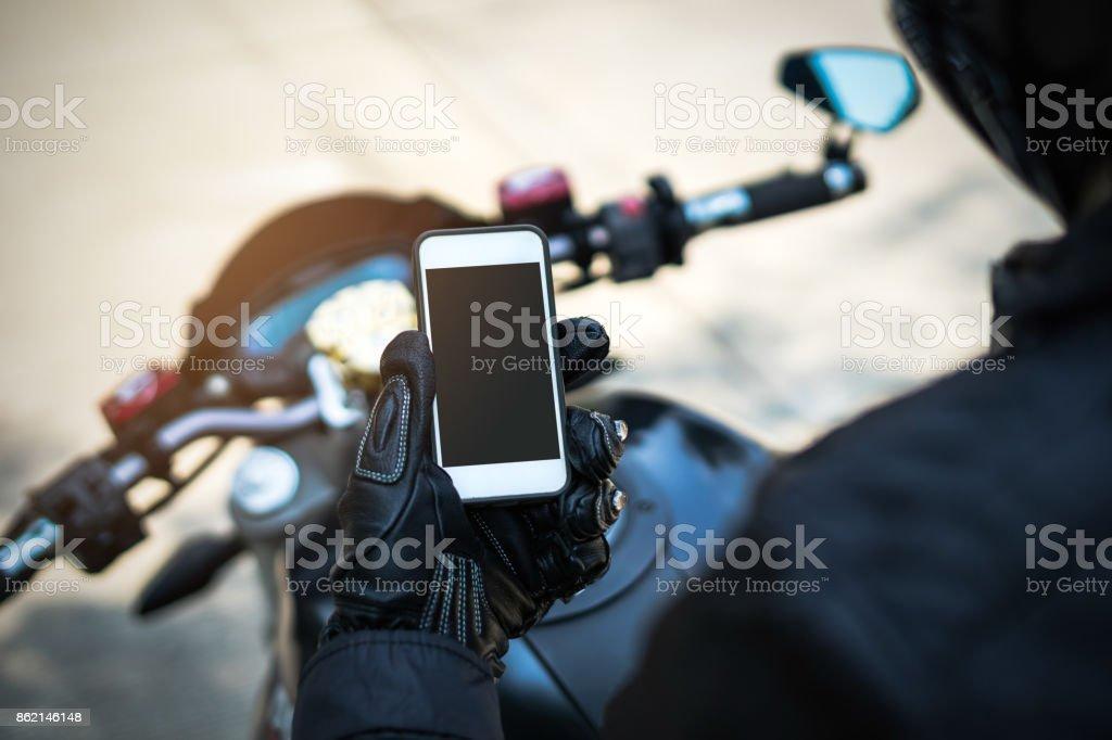 motociclista andar de moto e segurando o telefone inteligente - foto de acervo