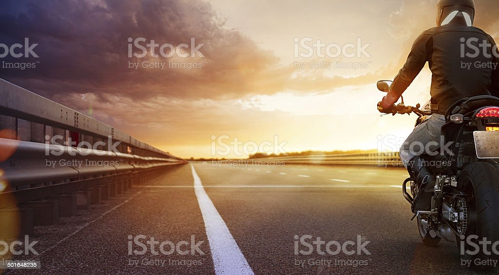 Biker riding motorcycle on an empty road at sunset stock photo