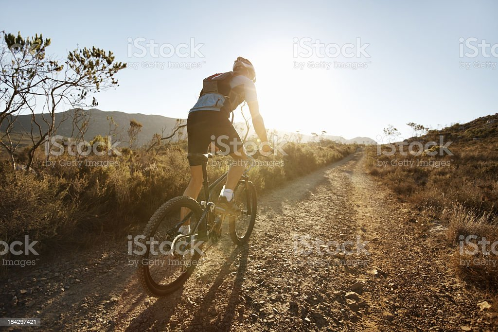 A biker riding on a gravel path at sunset stock photo