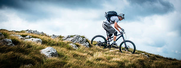Biker Riding on a Mountain Trail Low angle view of a mountain biker riding bike on a mountain trail along the edge of a ridge. mountain biking stock pictures, royalty-free photos & images