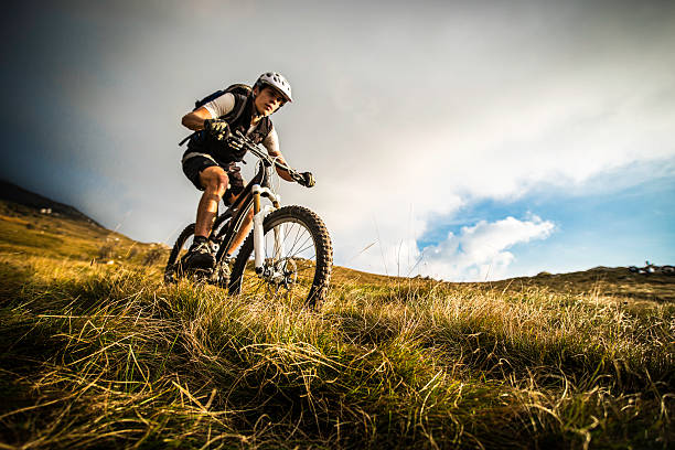 biker riding on a mountain trail - mountain biking stock pictures, royalty-free photos & images