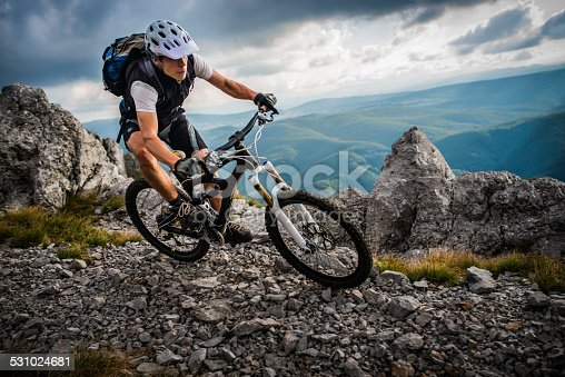 Mountain biker riding his bike down a rocky pathway with sharp grey rocks and ominous black clouds overshadowing green wavy hills in the background.