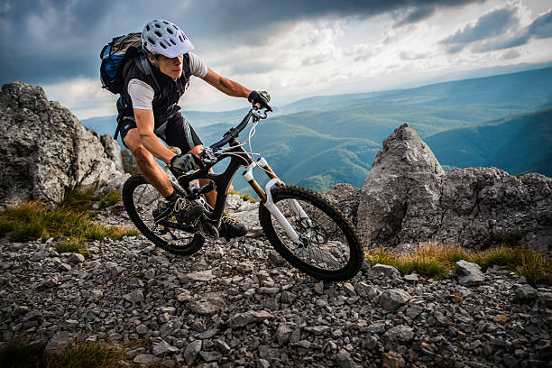 Biker Riding on a Mountain Trail Mountain biker riding his bike down a rocky pathway with sharp grey rocks and ominous black clouds overshadowing green wavy hills in the background. mountain bike stock pictures, royalty-free photos & images