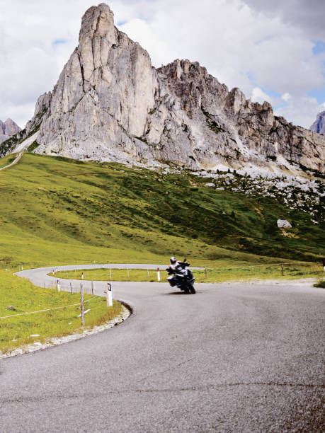 Biker Riding on Mountain Road in European Alps