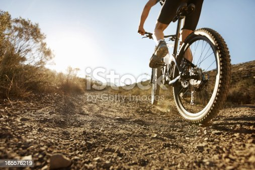 Low angle view of mountain biker riding a bike on a sunny day