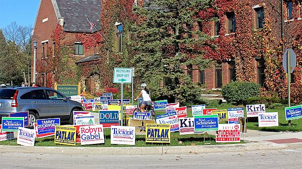 Biker riding through election political lawn signs outside polling place stock photo