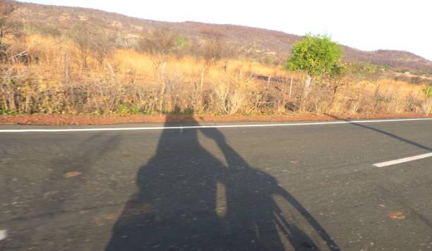 sombra de motociclista na estrada - motociclista стоковые фото и изображения