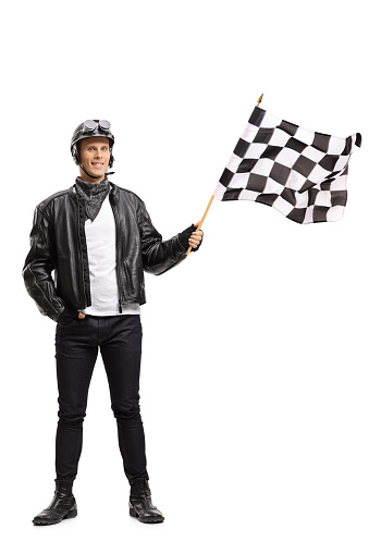 Full length portrait of a biker waving a checkered race flag isolated on white background