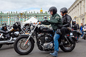 St. Petersburg, Russia - August 03,  2019: Harley-Davidson Motorcycle Festival in St. Petersburg. A couple of bikers  in helmets  rides along Palace Square on a motorcycle
