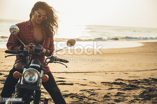 One man, handsome man sitting on his motorcycle on the beach, taking pictures with instant camera.