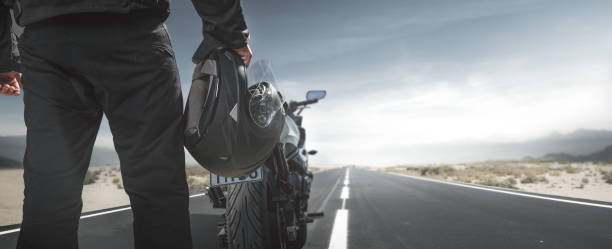 biker with motorcycle on a country road - crash helmet stock photos and pictures