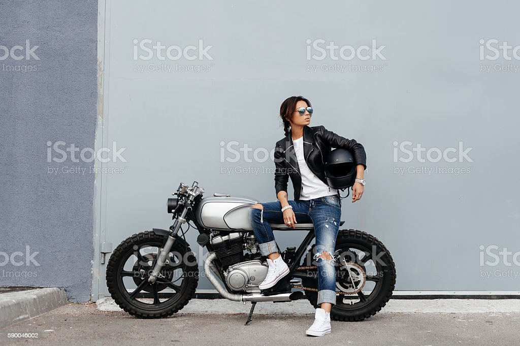 Biker woman in leather jacket on motorcycle stock photo