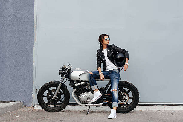 Biker woman in leather jacket on motorcycle - foto de stock