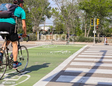 istock Bikers and pedestrians crosswalk in a sunny day 962659794