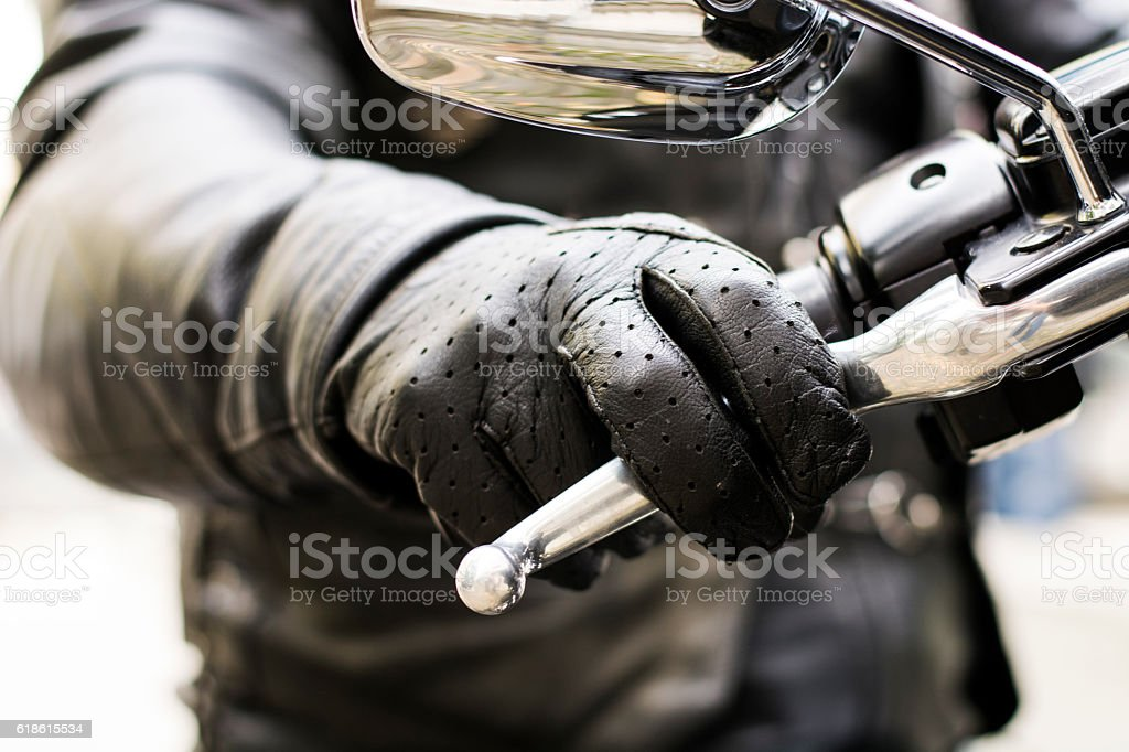 Biker's hand on brake lever handlebar stock photo