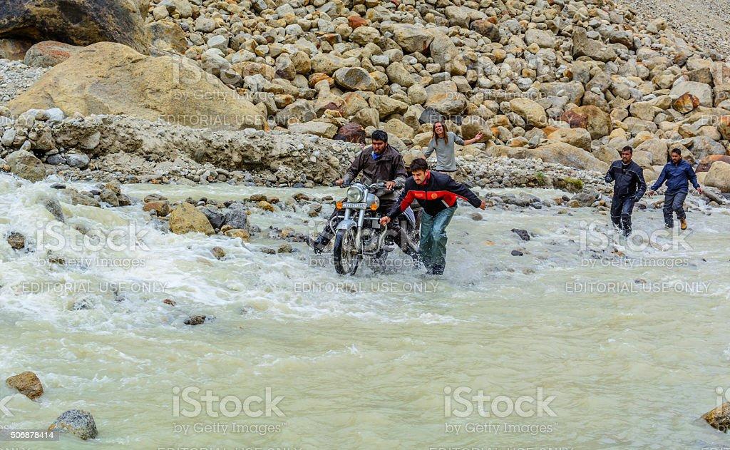 Ciclistas ajudar uns aos outros para atravessar a cascata na estrada - foto de acervo