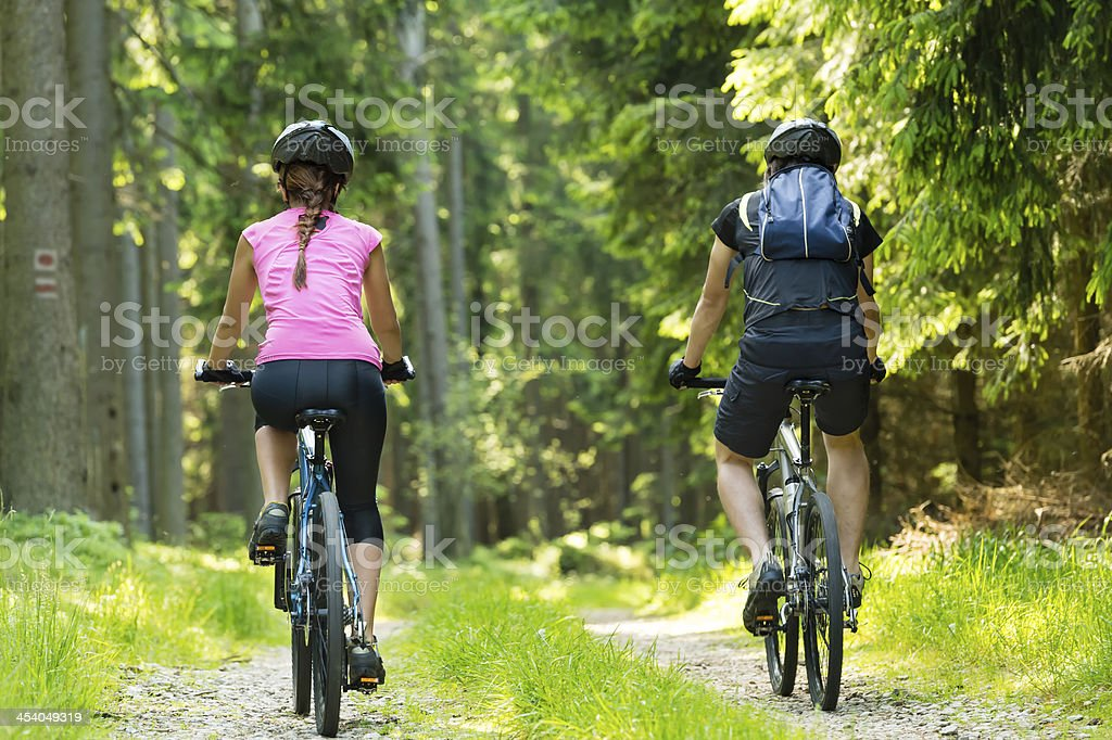 Bikers in forest cycling on track stock photo