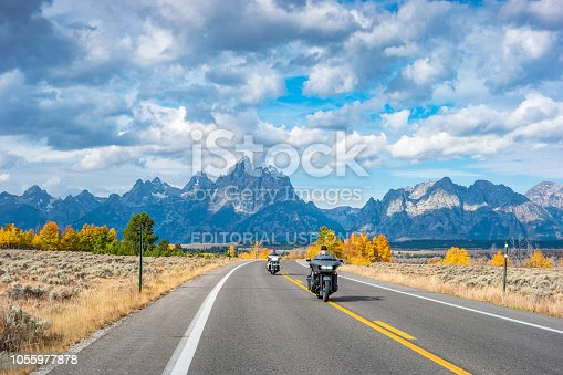 Bikers ride motorcycles in Grand Teton National Park, Wyoming, USA on a cloudy autumn day.