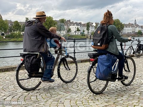 Maastricht, the Netherlands, - September 30, 2020. People on there bikes passing the Meuse river quay in the city of Maastricht.