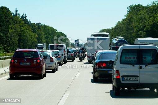Heidelberg, Germany - July 10, 2015: Some bikers on motorcycles are passing traffic jam on highway A5 in summer holiday time. Traffic is ruling to south. Bikers are driving in center between lanes.