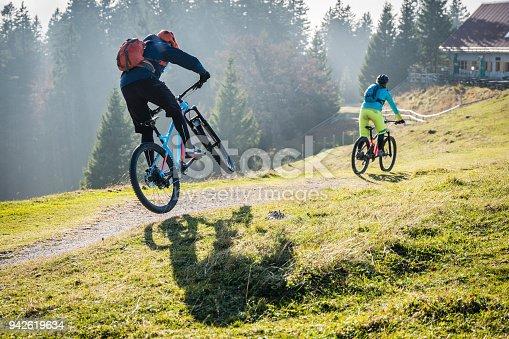 Bikers riding mountain bikes on mountain trail, male biker jumping with mountain bike.