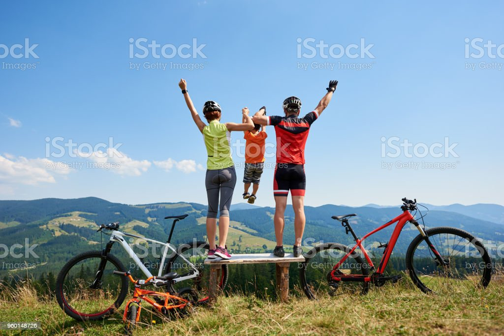 Bikers standing with raised hands, holding child in the air, resting after cycling bicycles stock photo