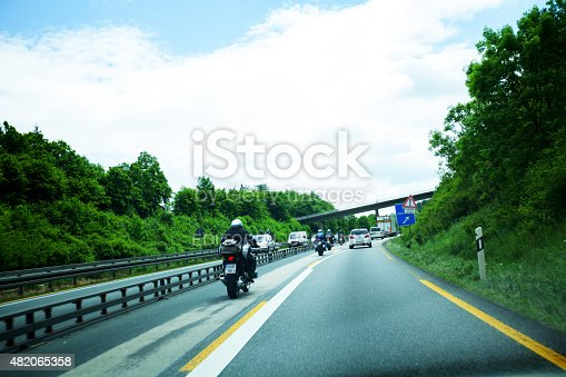 Dillenburg, Germany - June 3, 2015: Bikers with luggage and cars are driving through construction and restoring area on highway A45 direction south. At right sign is road sign for resting area Gaulskopf.