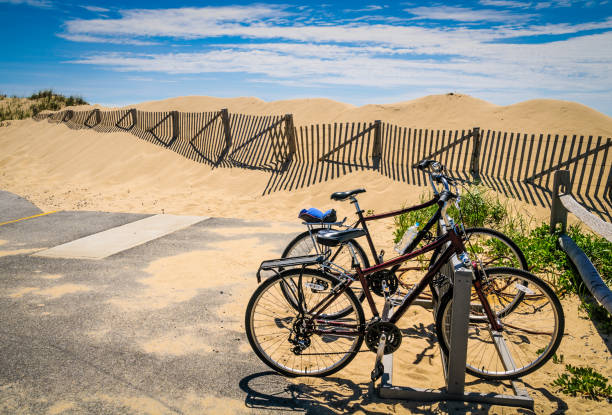Bikes at the Beach Two bicycles are parked in a bike rack near the beach along the Provincelands Bike Trail in Provincetown, Massachusetts.  Cape Cod is known for its extensive network of well maintained bicycle trails. provincetown stock pictures, royalty-free photos & images