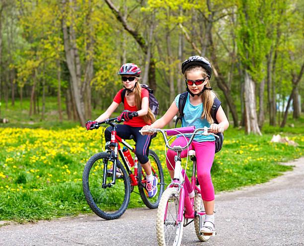 Bikes cycling girls with rucksack on bike lane. – Foto