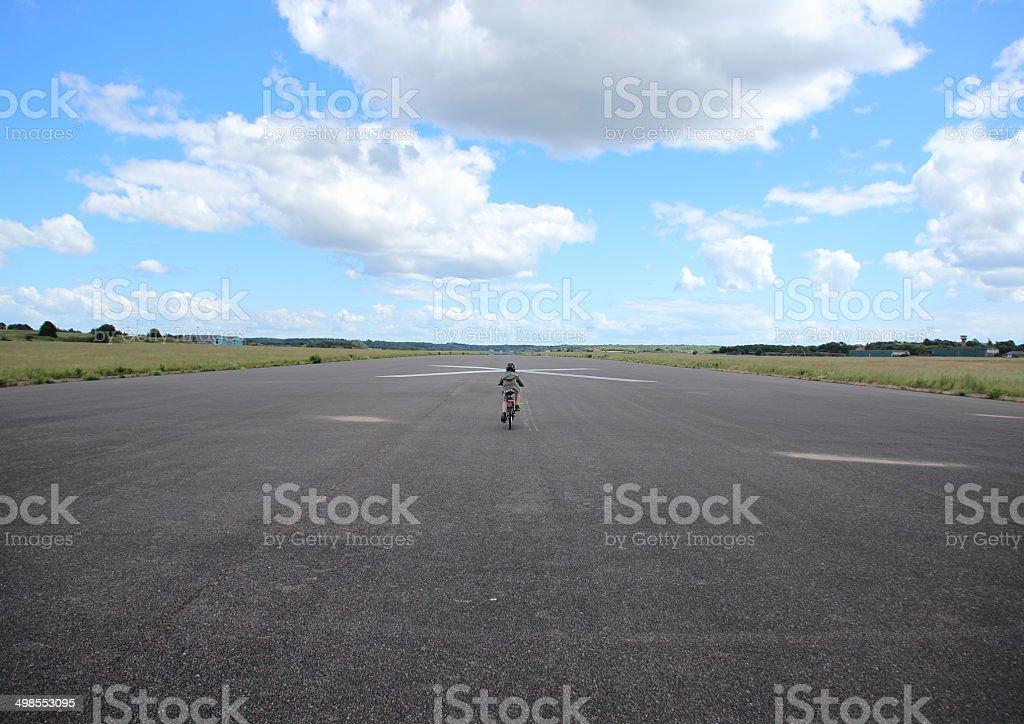 Biking child with helmet on airplane runway stock photo