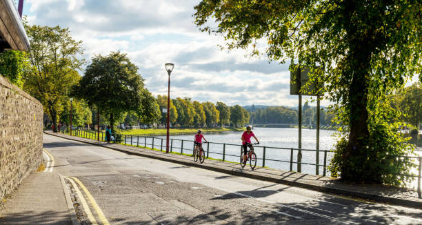 Biking riding in Inverness, Scotland Inverness, Scotland, UK. October 9, 2017. Two people riding bikes on a sidewalk alongside the river in Inverness Scotland. inverness scotland stock pictures, royalty-free photos & images
