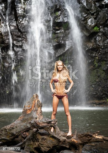 Beautiful woman with natural long hair standing in front of the breathtaking Ellinjaa Falls, Millaa Millaa, Queensland, Australia. Nikon D810. Converted from RAW.