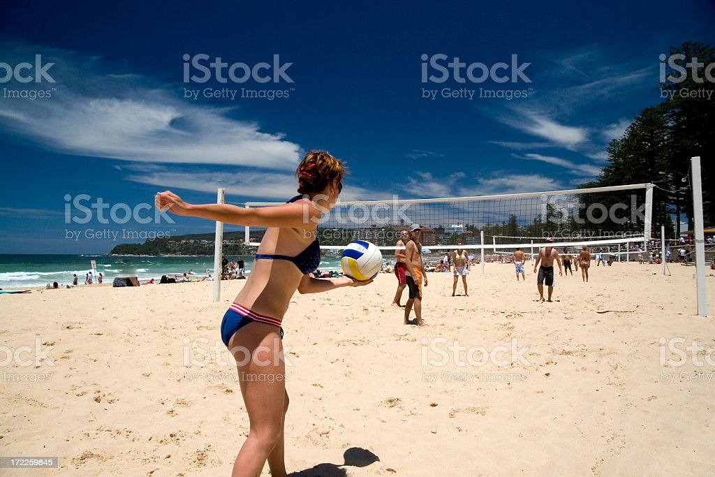 A bikini clad woman prepares to serve in beach volleyball stock photo