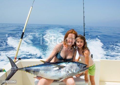 156872766 istock photo bikini fisher woman and daughter with bluefin tuna 159012043