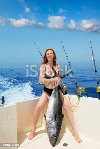 istock bikini fisher woman holding bluefin tuna on boat 155674939