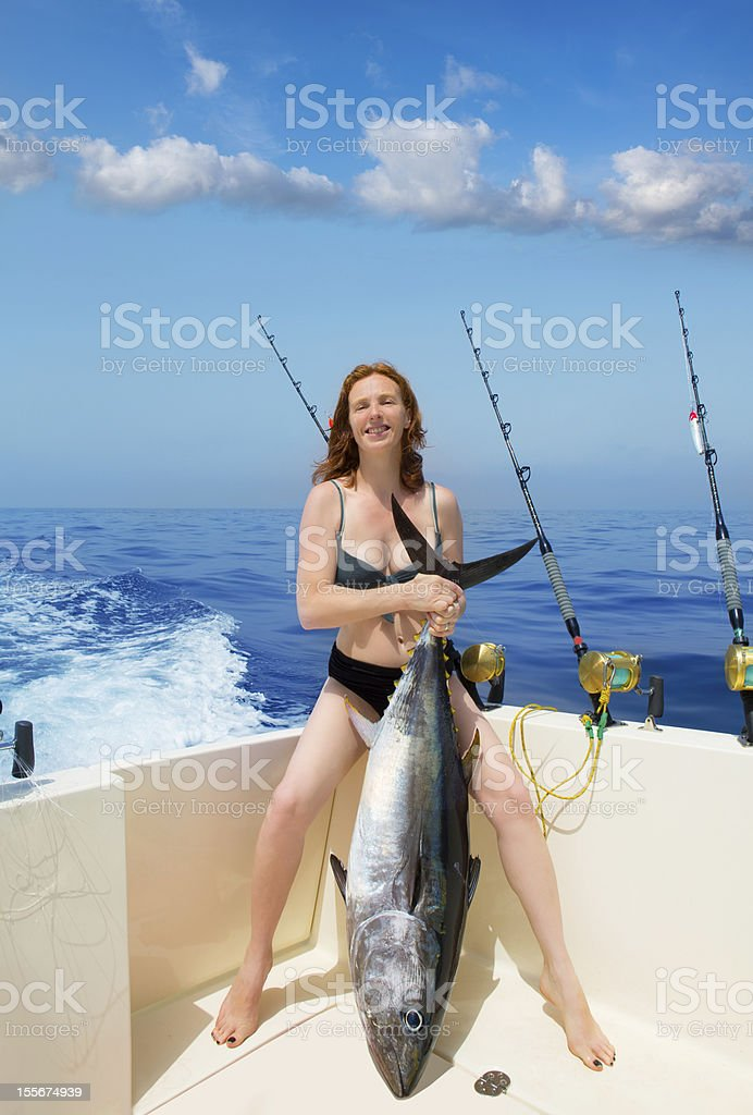 bikini fisher woman holding bluefin tuna on boat stock photo