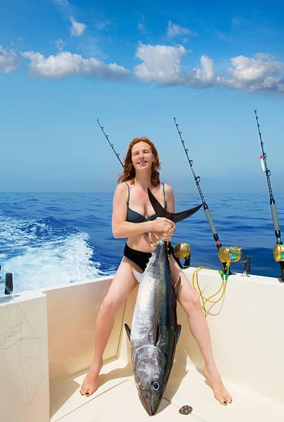 bikini fisher woman holding bluefin tuna on boat stock photo