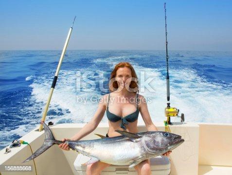 istock bikini fisher woman holding bluefin tuna on boat 156888668