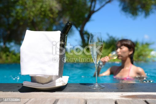 873264516istockphoto Bikini Girl Drinking Champagne In Swimming Pool 157720394
