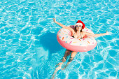 bikini girl in Santa Claus hat with sunglasses relaxed on pink inflatable pool ring. copy space.