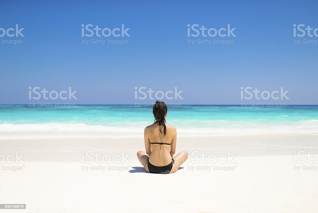 Bikini girl sitting on tropical beach paradise stock photo