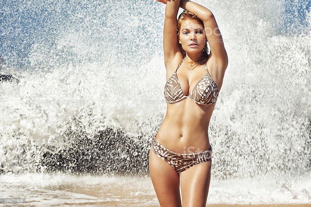 Bikini Model Posing on Remote Hawaiian Beach with Crashing Waves stock photo