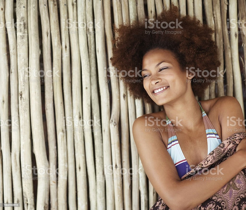 Bikini model smiles and leans against bamboo wall royalty-free stock photo