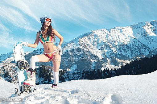 istock Bikini snowboarder meets spring on a slope in the mountains 1173572894