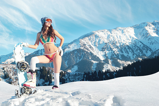 Bikini snowboarder meets spring on a slope in the mountains