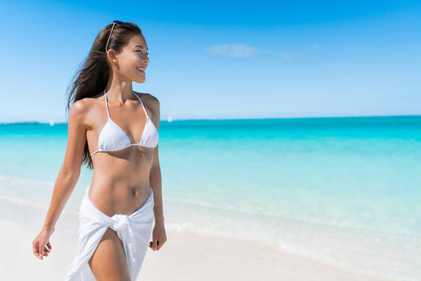 Bikini vacation woman relaxing in beach wear Bikini woman relaxing in white sun protection beachwear walking on tropical Caribbean beach with turquoise ocean water during summer vacations. Happy lifestyle Asian girl. bikini stock pictures, royalty-free photos & images